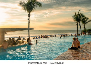 BALI, INDONESIA - FEBRUARY 4, 2013: Tourists enjoy a Bali vacation by the pool and beach. Bali is popular tourist destination in particular for Australian people.