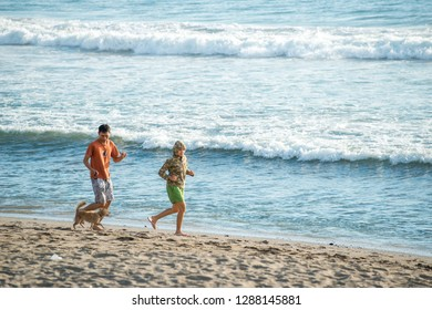 BALI, INDONESIA - FEBRUARY 4, 2013: Tourists enjoy a Bali vacation exercising with a dog on a beach. Bali is popular tourist destination in particular for Australian people.