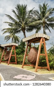 BALI, INDONESIA - JANUARY 14, 2018: Territory Discovery Candidasa Cottages and Villas Hotel with hanging wicker chairs at sunny day, Bali, Indonesia