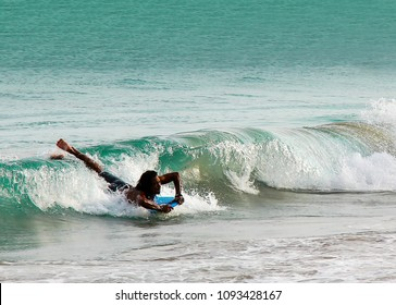 BALI, INDONESIA - January 7, 2015: Asian man surfer lay on surfboard on beautiful ocean wave. Catch and riding the waves.
