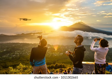 BALI, INDONESIA - JANUARY 7, 2018: Group of young people watch the dawn on top of the Batur volcano in Bali, Indonesia. Man pilotes UAV copter drone with digital camera for tacking picture or video.