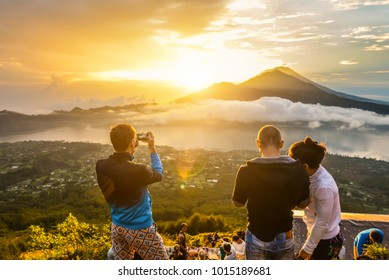 BALI, INDONESIA - JANUARY 7, 2018: Group of young people watch the dawn on top of the Batur volcano in Bali, Indonesia.
