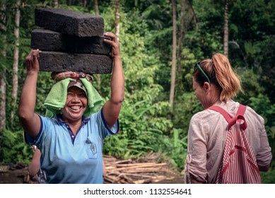 BALI, INDONESIA - JANUARY 9, 2018: Balinese woman works hard at extraction of natural stone in Bali, she carries stones from the quarry on her head