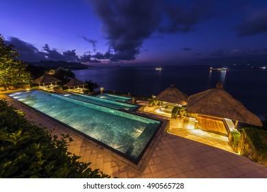 BALI, INDONESIA - Jul 24, 2016: Swimming pool of luxury hotel during sunrise.