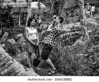 BALI, INDONESIA, JULY 14, 2017: A young couple in love enjoying in Bali, the man enthusiastically photographing his love.