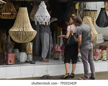 BALI, INDONESIA, JULY 17, 2017: A lady bargaining with shop keeper in Bali, Indonesia while her boyfriend getting amorous and kissing her neck.