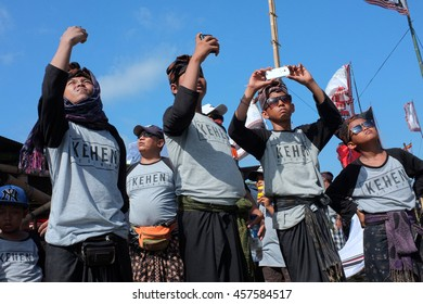 BALI, INDONESIA - JULY 24: Young boys photograph and film a traditional kite-flying competition with their smart phones on July 24, 2016 near Sanur Beach, Bali, Indonesia.