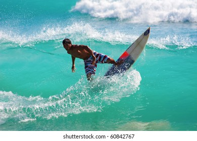 BALI, INDONESIA - JULY 27: Unidentified young man surfing the waves on July 27, 2010. Dreamland beach, Bali, Indonesia. The Dreamland is one of the most popular surfing areas of Bali.