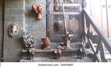 Bali, Indonesia; July 30, 2013: The recieving area of a spa in Ubud contains several things of interest - statues made of wood, clay, and stone, and intricate carvings on doors and hand rails.