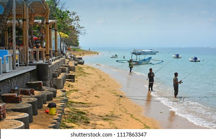 Bali, Indonesia - June 03, 2018; Fishermen with rods right in front of the cafes and bars on Sanur Beach, Bali Indonesia.