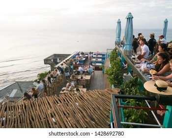 Bali, Indonesia - June 1 2019: Patrons enjoy a sea view at the Single Fin bar and restaurant in Uluwatu.