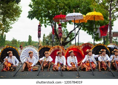 Bali, Indonesia - June 23, 2018: Group of young dancer men in ethnic costumes with traditional red, black and yellow umbrellas on hindu ceremony parade during temple festival. Balinese people culture.