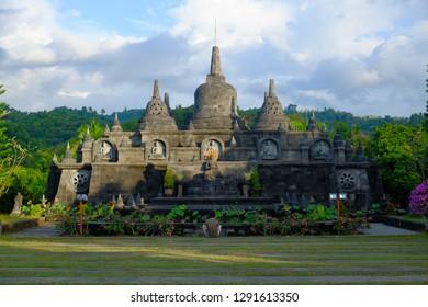BALI, INDONESIA. June 27, 2017. Tourist meditating before a  Buddhist Temple Brahmavihara Arama, located near Singaraja, a few kilometers from the Banjar hot springs, in the north of Bali.