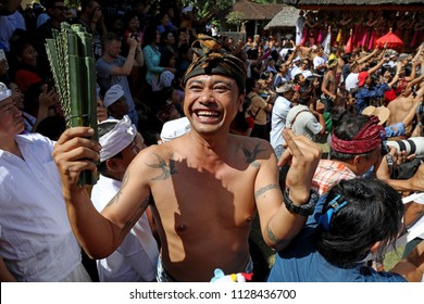 Bali, Indonesia – June 30 2018: A man holds a bunch of pandan leaves ahead of taking part in ritual fights using the leaves in the village of Tenganan, Bali during the annual Perang Pandan festival