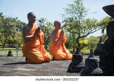 BALI, INDONESIA - MAR 26: Buddhist monks in orange robe praying in Brahma Vihara Arama Buddhist Monastery 26 March 2015 in Bali, Indonesia