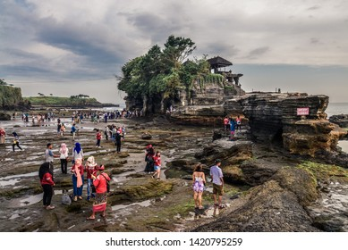 Bali, Indonesia - March 11, 2019: People walkin  near the Tanah Lot Temple, the most important indu temple of Bali, Indonesia befor sunset
