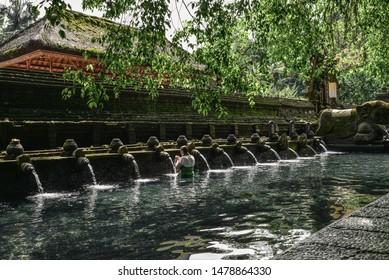 BALI, INDONESIA - MARCH 17, 2019: woman praying in holy spring water of sacred pool at Pura Tirta Empul Temple, Tampaksiring, Bali, Indonesia.