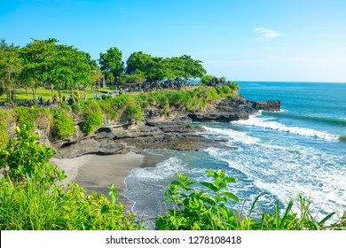 Bali, Indonesia - March 24, 2017: People on  the path that leads to the Tanah Lot temple on the shores of the sea