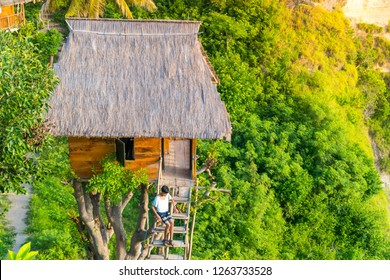 BALI, INDONESIA - MARCH 24, 2018: Tourist sitting at the stairs of Tree House (Rumah Pohon) , at Atuh Beach, Nusa Penida, Bali, Indonesia