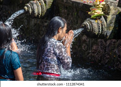 BALI, INDONESIA - MARCH 29, 2015 : Unidentified Balinese families come to the sacred springs water temple of Tirta Empul in Bali, Indonesia to pray and cleanse their soul