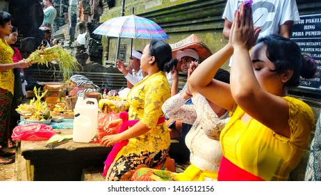 Bali, Indonesia - MAY 10, 2017: Some local people are praying for their god at Tirta Empul Temple, wearing beautiful traditional clothes with some offerings in front of them.
