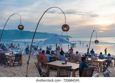 Bali, Indonesia - May 12, 2017: Jimbaran tropical beach is a main popular balinese attraction, famous for the clear, aqua blue water and sea food restaurants in Bali, Indonesia.