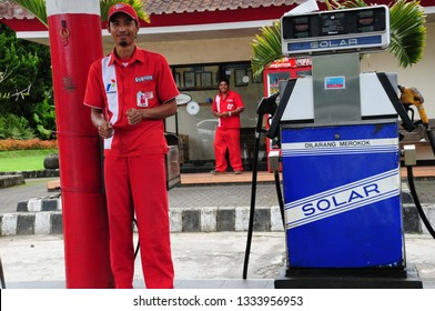 Bali / Indonesia - May 2, 2010: Pertamina Petrol / Gas Station attendant in colorful uniform in central Bali
