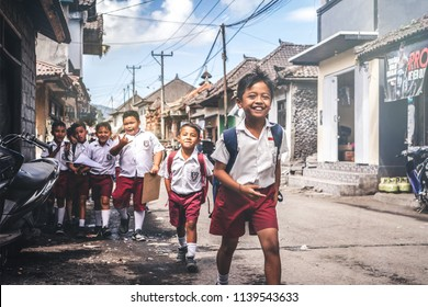 BALI, INDONESIA - MAY 23, 2018: Group of balinese schoolboys in a school uniform on the street in the village.