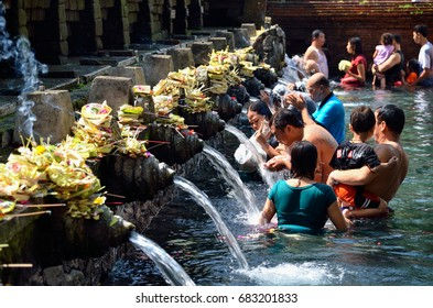 BALI (INDONESIA) – MAY 24, 2014 : Balinese ritual purification in the pool of Tirta Empul Temple.