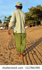 Bali, Indonesia - May 29 2018; Balinese man grooms Sanur beach with a rake in the early morning.