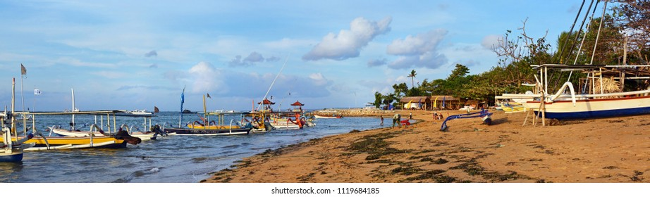 Bali, Indonesia - May 29, 2018; Colorful early morning Bali Fishing Boats and People Panorama on Sanur beach, Indonesia.