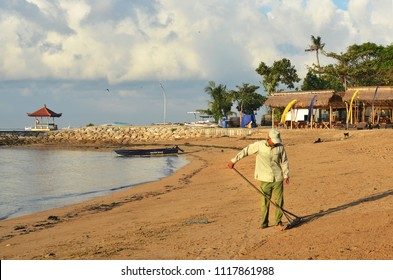 Bali, Indonesia - May 30, 2018; Balinese man grooms Sanur beach with a rake in the early morning.