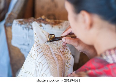 BALI, INDONESIA - NOVEMBER 3RD 2014 : Balinese man use watercolor to color on the fabric to make Batik. Batik-making is part of Indonesian culture and tourist attraction in Bali, Indonesia.