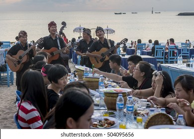 Bali, Indonesia - Oct 08 2016: Group of musicians entertain tourists while enjoy seafood dinner served on the beach during sunset at Jimbaran beach.
