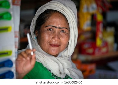 Bali, Indonesia - October 12, 2018: A woman shopkeeper holding a cigarette in Bali, Indonesia poses for a portrait picture.
