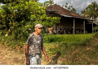 Bali, Indonesia - October 23rd 2015: Wise old Balinese man looking very serious while walking through a local village wearing camouflage clothing and a cap in Bali, Indonesia, Asia