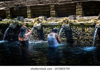 Bali, Indonesia - October 23rd 2015: Balinese Hindus washing in a ritual purification bath with holy spring water from stone sculptured fountain showers at Tirta Empul Temple in Bali, Indonesia, Asia
