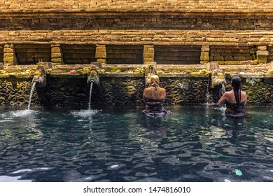 Bali, Indonesia - October 23rd 2015: Two female tourists washing in a ritual purification bath with holy spring water from stone sculptured showers at Tirta Empul Temple in Bali, Indonesia, Asia