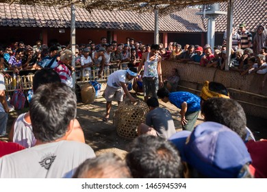 Bali, Indonesia - October 28th 2015: Traditional cock fight with the cockerels in a basket before the fight and a crowd of men gathered around watching and gambling