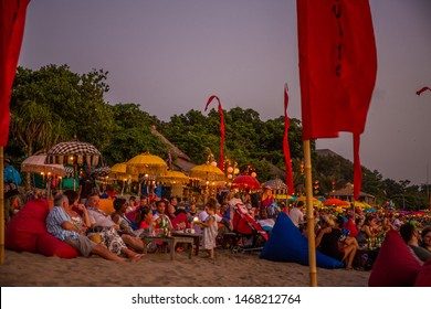 Bali, Indonesia - October 31st 2015: Crowd of tourists sitting & relaxing on bean bags on a beach at sunset while socialising & drinking beers at Seminyak Beach in Bali, Indonesia, Asia