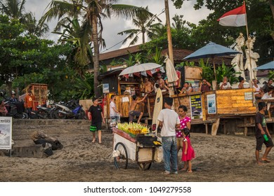 BALI, INDONESIA - OCTOBER 5, 2016: Vendor is selling food on Canggu beach, and people nearby are drinking beer in the beach bar