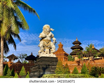 Bali indonesia, public statue photographed from road, hindu gods statue, coconut tree and blue skys.