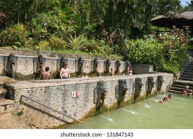 BALI, INDONESIA - SEP 20: People take a bath in termal Banjar Tega hot springs on Sep 20, 2012 in Banjar, Bali, Indonesia. Springs are popular tourist attraction on North Bali.