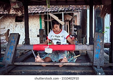 Bali, Indonesia - Sep 21, 2019: Weaver young woman behind a loom, handmade manufacturing fabric and carpets. Handmade on a wooden loom manufacturer of thread, fabric and carpets. Close-up.