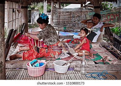 Bali, Indonesia - Sep 21, 2019: Weaver young woman behind a loom, handmade manufacturing fabric and carpets. Handmade on a wooden loom manufacturer of thread, fabric and carpets.