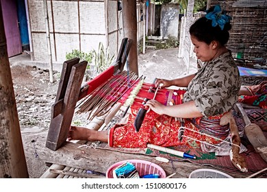 Bali, Indonesia - Sep 22, 2019: Weaver young woman behind a loom, handmade manufacturing fabric and carpets. Handmade on a wooden loom manufacturer of thread, fabric and carpets.