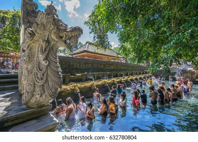 Bali, Indonesia - Sept. 9, 2017. Guardian Sculpture and worshippers during cleansing ceremony at Pura Tirta Empul temple. Famous for its Holy Spring Waters