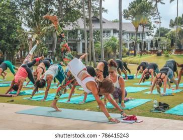 Bali, Indonesia - September 10, 2017:  Female Yoga Teacher Guiding an Outdoor Yoga Class Guiding Students into Three-Legged Downward Dog Pose