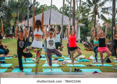 Bali, Indonesia - September 10, 2017:  Female Yoga Teacher Guiding an Outdoor Yoga Class Leading Students into Tree Pose
