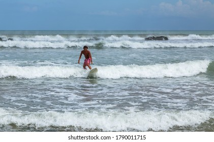 Bali, Indonesia - September 17, 2019: Surfer man on a sandy beach with a surfboard. Beach, sea, bright sunny day. Summer lifestyle